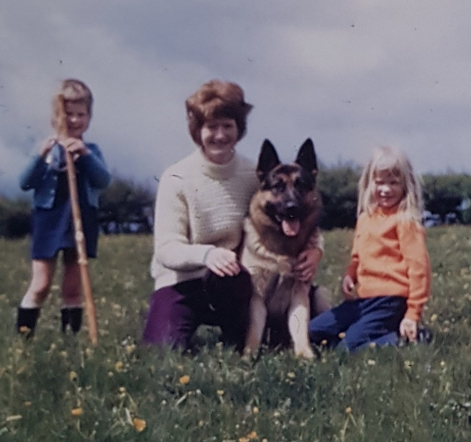 Myeloma patient Maureen many years ago in a field with her daughters on either side of her and with her German Shepherd dog