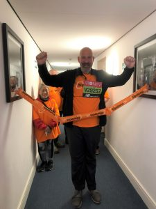 Myeloma patient Charles walking through a finish line at home. He is wearing an orange Myeloma UK t-shirt with his arms raised in the air and smiling